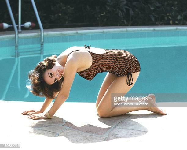 Natalie Wood US actress wearing a brown swimsuit kneeling beside a swimming pool circa 1970