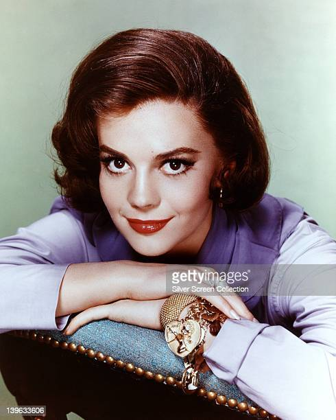 Natalie Wood US actress wearing a lilac blouse with a gold bangle and a gold charm bracelet on her left wrist resting her chin on her hands in a...