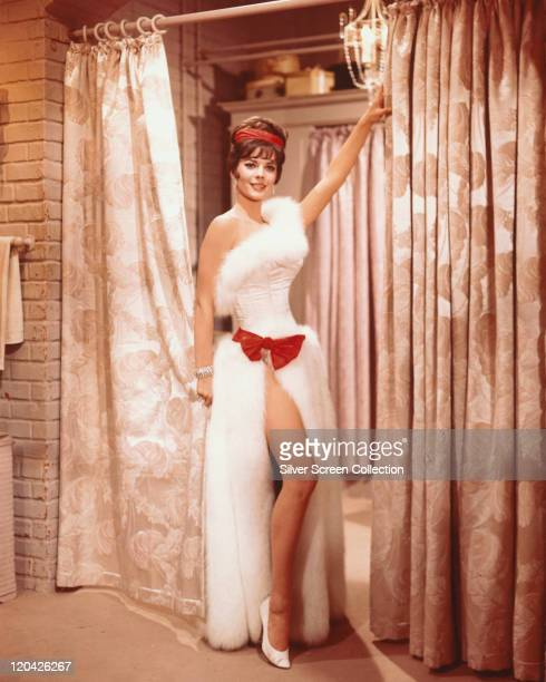 Natalie Wood US actress wearing a long white splitskirt dress with white fur trim and a red bow her leg exposed through the split in a publicity...