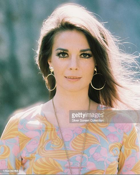Natalie Wood US actress wearing a print pattern top with a large gold necklace and gold hoop earrings circa 1975