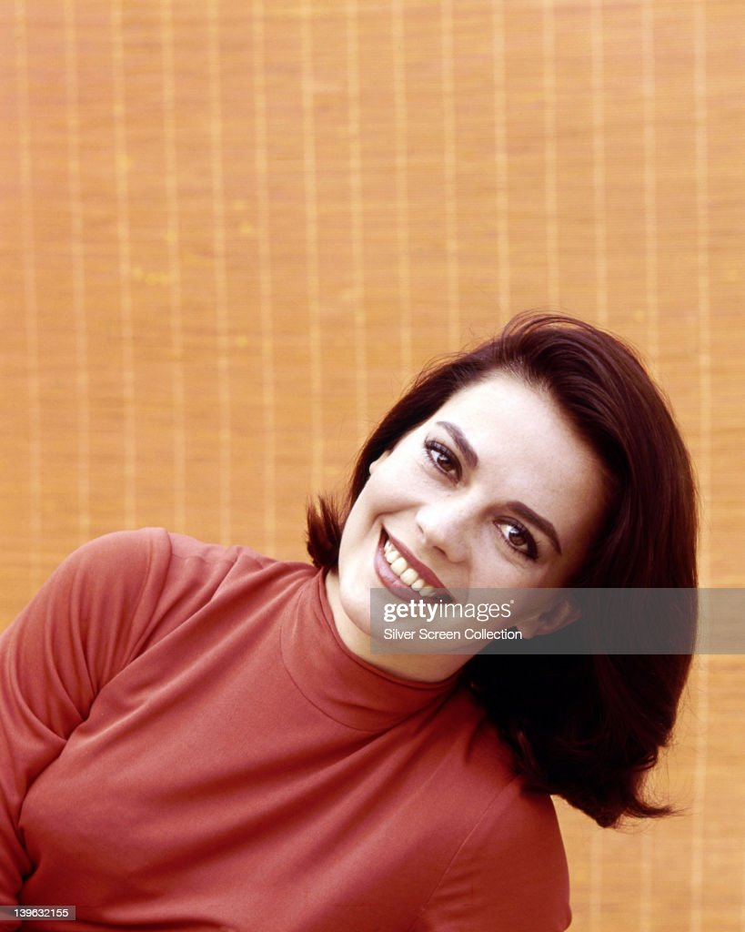 Natalie Wood (1938-1981), US actress, wearing a red top, smiling in a studio portrait, against a yellow background, circa 1965.