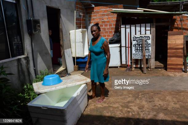 Natalina Vasconcelos, an autonomous salesperson, poses for a photo next to a Styrofoam cooler she uses to store water during a blackout due to fire...