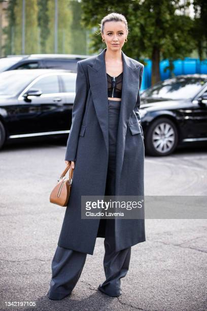Nataly Osmann, wearing grey coat, grey pants, black crop top and brown bag, poses ahead of the Boss fashion show during the Milan Fashion Week -...