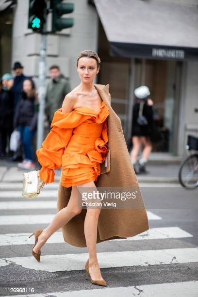 Nataly Osmann wearing orange ruffled dress attends the Ermanno Scervino show at Milan Fashion Week Autumn/Winter 2019/20 on February 23 2019 in Milan...