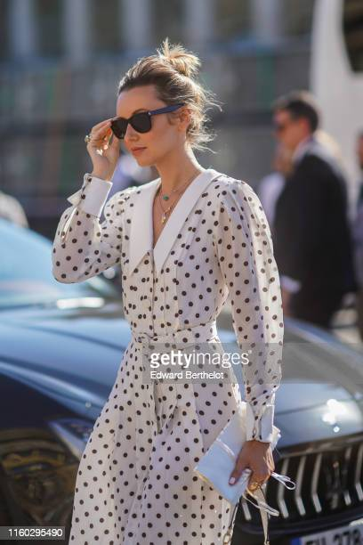 Nataly Osmann wears sunglasses necklaces a sailor collar white dress with black polka dots outside Armani during Paris Fashion Week Haute Couture...