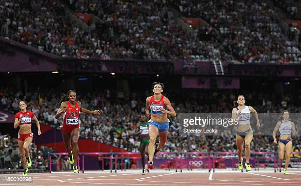 Natalya Antyukh of Russia crosses the finish line ahead of Lashinda Demus of the United States in the Women's 400m Hurdles Final on Day 12 of the...