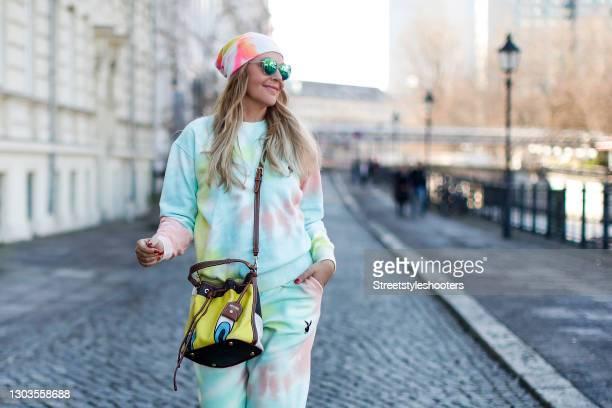 Natascha Ochsenknecht wearing a Tweety Bird bag by Moschino, a pastel tie dye sweatshirt by Playboy, pastel tie dye sweatpants by Playboy, a pastel...