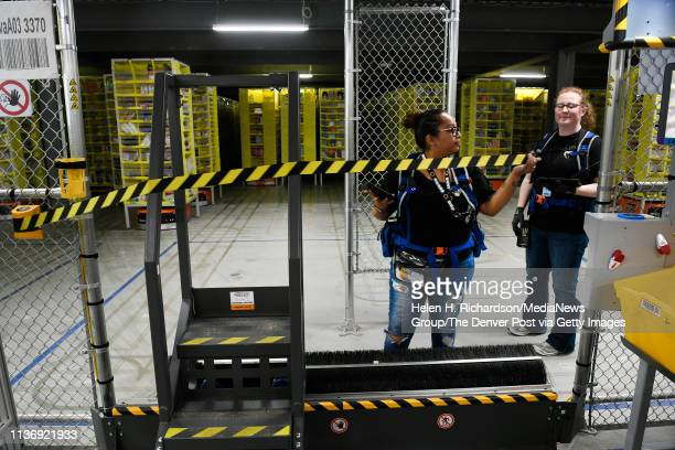 Natasha Cruz middle and Amanda Fields both warehouse associates wear specialized robotic vests that allows them to access Amazon's robotic floors...