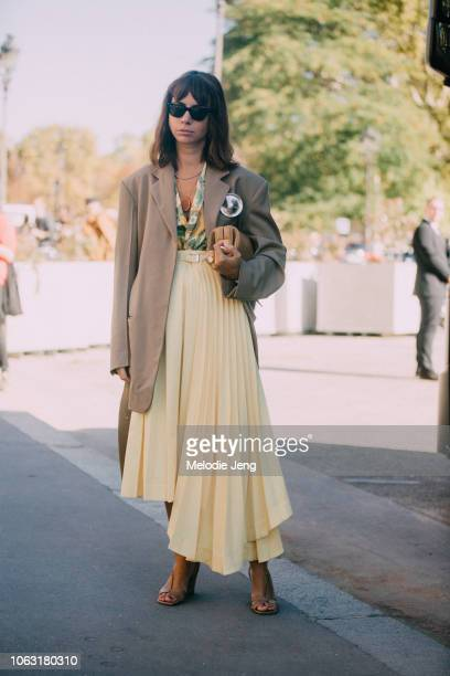Natasha Goldenberg in a brown blazer and yellow pleated skirt during Paris Fashion Week Spring/Summer 2019 on September 26 2018 in Paris France