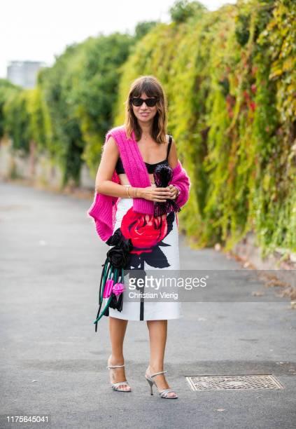 Natasha Goldenberg is seen wearing white skirt with black print, net bag, pink cardigan outside the Prada show during Milan Fashion Week...