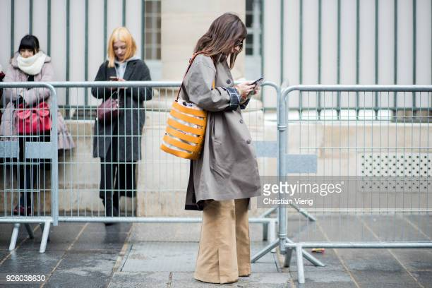 Natasha Goldenberg looking at her phone wearing beige wide leg pants grey coat Paco Rabanne bag puffer jacket is seen outside Ann Demeulemeester on...
