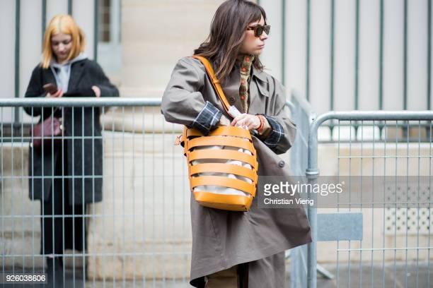 Natasha Goldenberg searching her bag wearing beige wide leg pants grey coat Paco Rabanne bag puffer jacket is seen outside Ann Demeulemeester on...