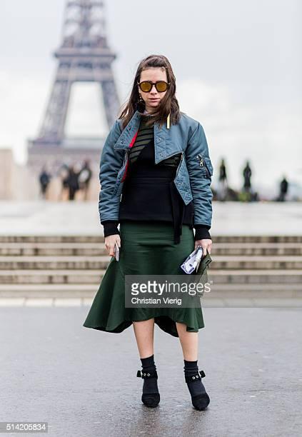 Natasha Goldenberg wearing a bomber jacket and green skirt posing in front of Eifel Tower outside Sacai during the Paris Fashion Week Womenswear...