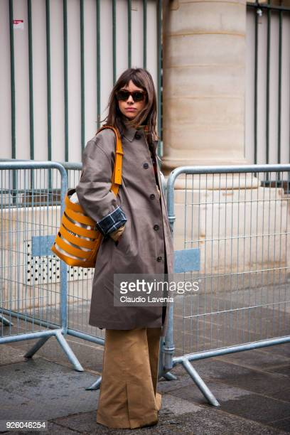 Natasha Goldenberg wearing a brown trench and yellow stripped bag is seen in the streets of Paris before the Ann Demeulemeester show during Paris...