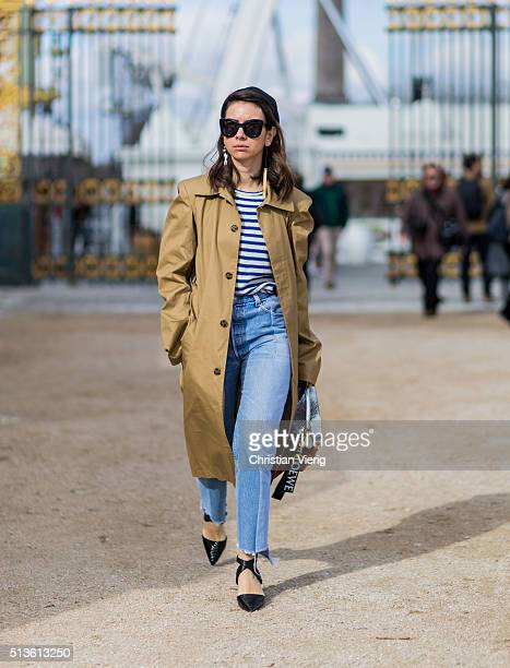 Natasha Goldenberg wearing a trench coat and blue denim jeans black heels and a Loewe bag outside Carven during the Paris Fashion Week Womenswear...