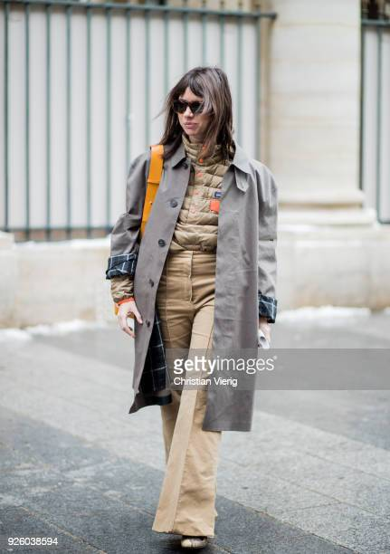 Natasha Goldenberg wearing beige wide leg pants grey coat Paco Rabanne bag puffer jacket is seen outside Ann Demeulemeester on March 1 2018 in Paris...
