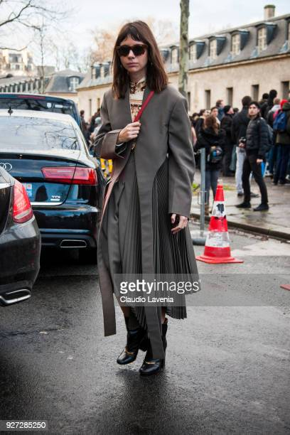 Natasha Goldenberg wearing green jacket and skirt and black heels boots is seen in the streets of Paris after the Valentino show during Paris Fashion...