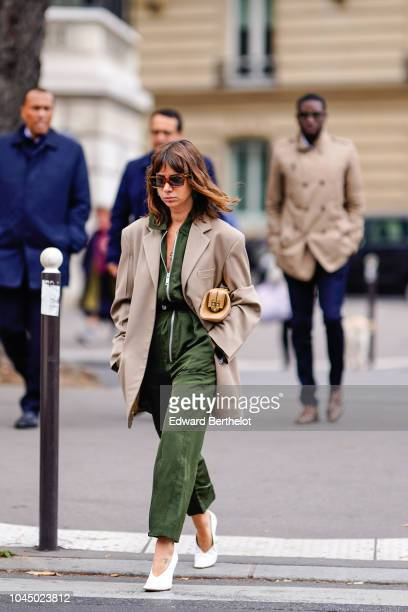 Natasha Goldenberg wears a beige blazer jacket a green jumpsuit sunglasses white shoes outside Miu Miu during Paris Fashion Week Womenswear...