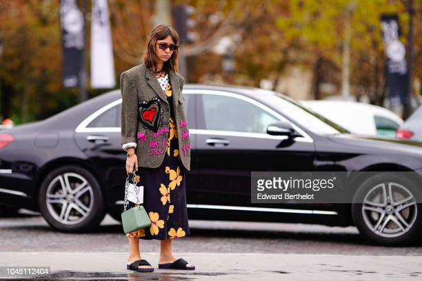Natasha Goldenberg wears a blazer jacket with embroidered pink words and an embroidered red heart a black dress with yellow floral print a green bag...
