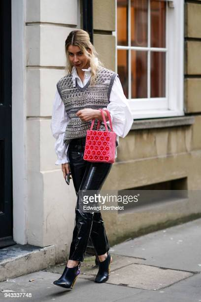 Natasha Goldenberg wears a white shirt a red bag a wool pattern sleeveless pull over black pvc plastic pants black shoes during London Fashion Week...