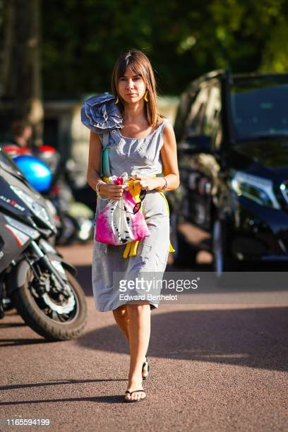 Natasha Goldenberg wears earrings a light grey dress with a scoop neckline and embellished with a large fabric flower black flipflops and tied a...
