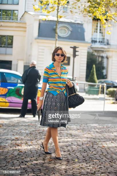 Natasha Goldenberg wears purple sunglasses, a blue and yellow striped Miu Miu polo cardigan, gray pleated gromet skirt, black heels, and a black Miu...