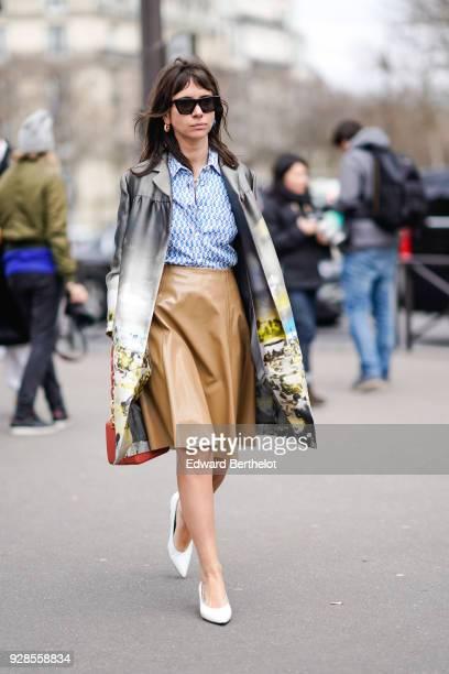 Natasha Goldenberg wears sunglasses a coat a blue shirt a brown leather skirt white shoes outside Miu Miu during Paris Fashion Week Womenswear...