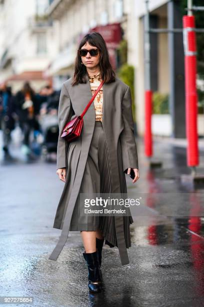Natasha Goldenberg wears sunglasses a gray pleated dress a red shoulder strap bag outside Valentino during Paris Fashion Week Womenswear Fall/Winter...