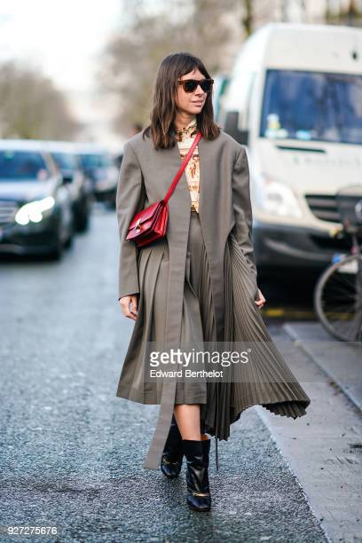 Natasha Goldenberg wears sunglasses a gray pleated dress a red shoulder strap bag outside Valentino during Paris Fashion Week Womenswear Fall/Winter...