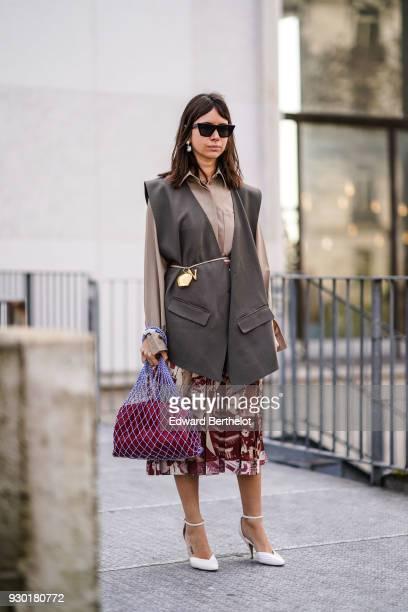 Natasha Goldenberg wears sunglasses a sleeveless blazer jacket a purple fishnet bag a printed skirt white shoes outside Giambattista Valli during...