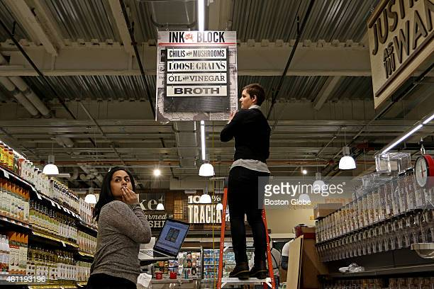 Natasha Jain left of Haverhill looks back down the aisle as Meghann Brideau of Roslindale puts up signage at the new Whole Foods Market in South End...