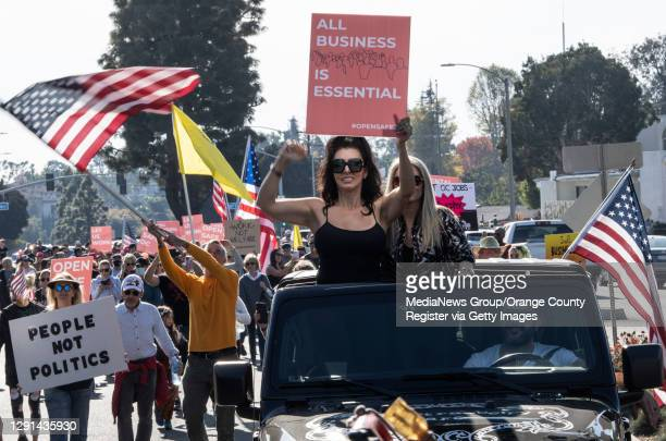 Natasha Kazic protests business closures as her husband, Alex Perisic, drives during a march down 17th street on Sunday, December 13, 2020. The...