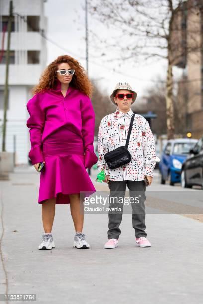 Natasha Zinko wearing a pink jacket with matching skirt and grey sneakers and Hamborghini Ivan wearing and printed shirt grey pants pink sneakers...