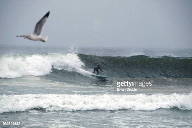Nate Arkwood surfs at Rockaway Beach during a snow storm March 21, 2018 in the Queens borough of New York. New York City and much of New England has...
