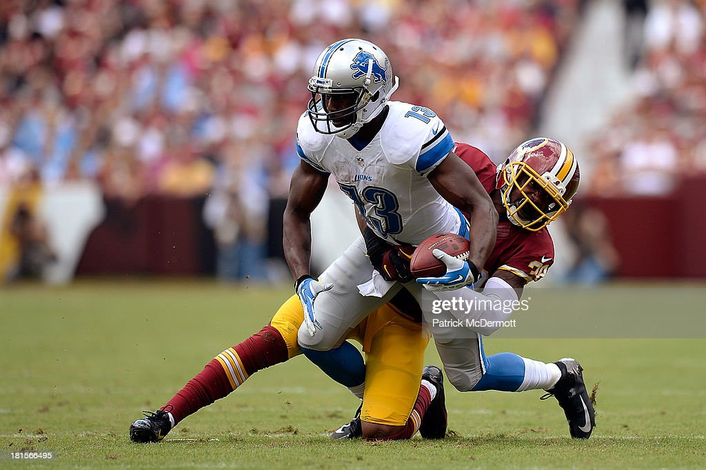 Nate Burleson #13 of the Detroit Lions is tackled by David Amerson #39 of the Washington Redskins after catching a pass from Matthew Stafford #9 (not pictured) in the first quarter during a game at FedExField on September 22, 2013 in Landover, Maryland.