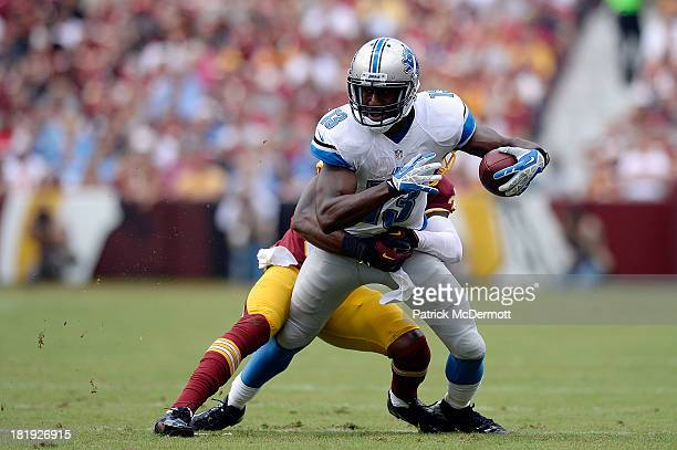Nate Burleson of the Detroit Lions is tackled by David Amerson of the Washington Redskins after catching a pass from Matthew Stafford in the first...