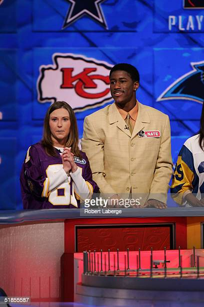 Nate Burleson of the Minnesota Vikings looks on with his favorite Vikings fan during the Wheel of Fortune NFL Players Week taping on December 7 2004...