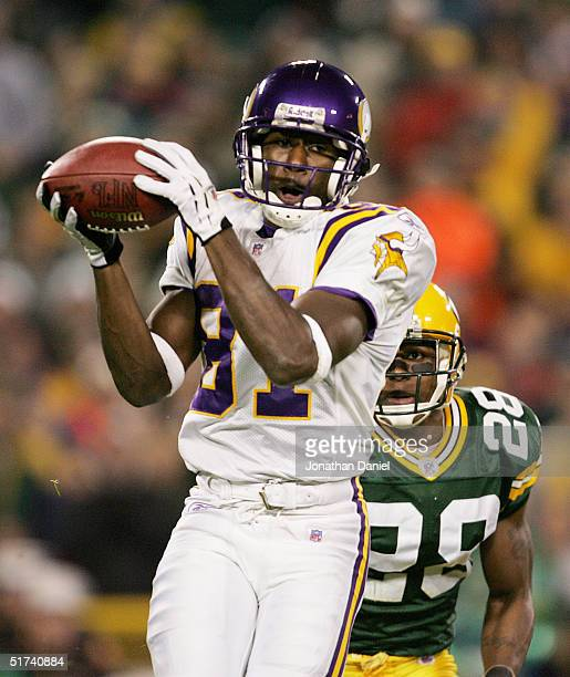 Nate Burleson of the Minnesota Vikings makes a reception as Ahmad Carroll of the Green Bay Packers looks on during a game at Lambeau Field on...