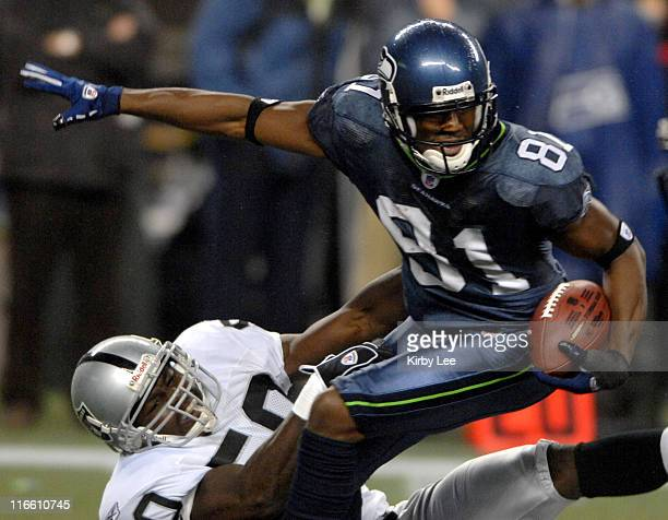 Nate Burleson of the Seattle Seahawks tries to break free from grasp of Isaiah Ekejiuba during 160 Seahawk victory in ESPN Monday Night Football game...