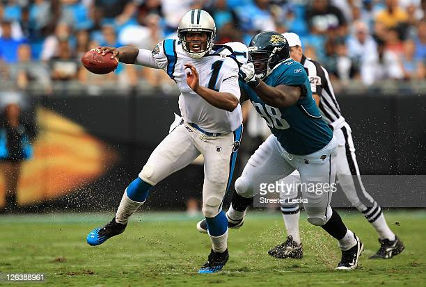 Nate Collins of the Jacksonville Jaguars tries to tackle Cam Newton of the Carolina Panthers during their game at Bank of America Stadium on...