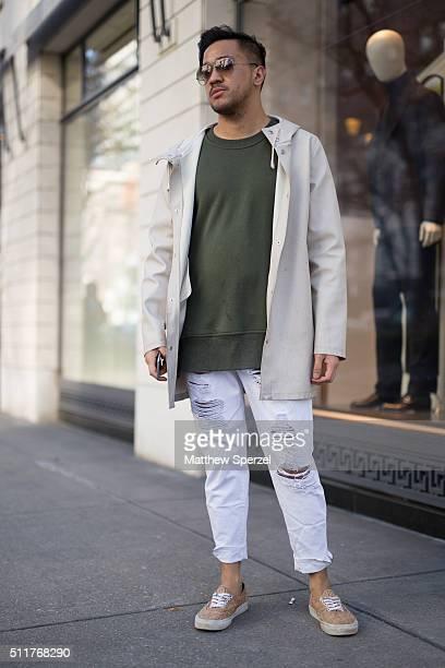 Nate Cruz is seen on Oak Street wearing Ray Ban glasses, beige Stutterheim jacket, army green Iridium sweater, white torn Topshop pants, and cork...