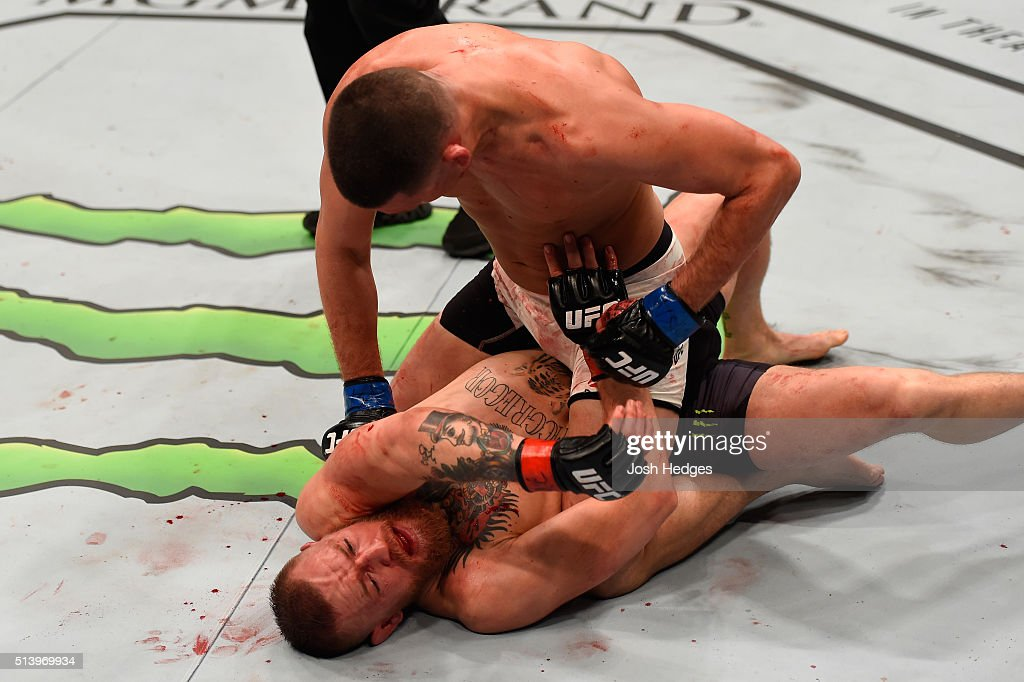 Nate Diaz (top) punches Conor McGregor of Ireland in their welterweight bout during the UFC 196 event inside MGM Grand Garden Arena on March 5, 2016 in Las Vegas, Nevada.