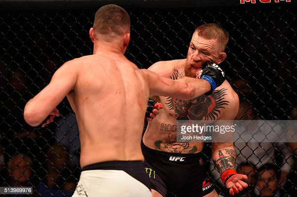 Nate Diaz punches Conor McGregor of Ireland in their welterweight bout during the UFC 196 event inside MGM Grand Garden Arena on March 5 2016 in Las...