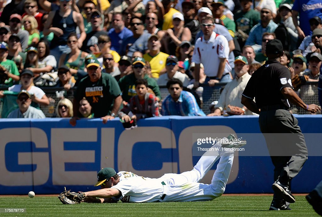 Nate Freiman #7 of the Oakland Athletics goes into a slide in foul territory but is unable to hold on to the ball off the bat Craig Gentry #23 of the Texas Ranger in the seventh inning at O.co Coliseum on August 4, 2013 in Oakland, California.