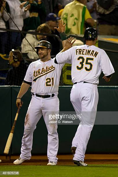 Nate Freiman of the Oakland Athletics is congratulated by Stephen Vogt after scoring a run against the Toronto Blue Jays during the eighth inning at...