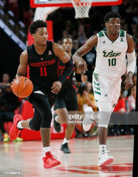 Nate Hinton of the Houston Cougars brings the ball up the court as Alexis Yetna of the South Florida Bulls follows during the second half at Fertitta...