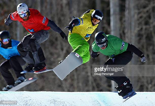 Nate Holland of the United States races to first place in the finals of the men's Snowboarder X ahead of Konstantin Schad of Germany in third place...