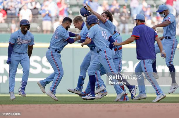 Nate Lowe of the Texas Rangers celebrates with teammates after hitting the game winning walk off single against the Baltimore Orioles during the...