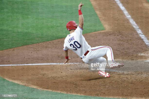 Nate Lowe of the Texas Rangers scores the winning run against the San Francisco Giants during the eleventh inning at Globe Life Field on June 9, 2021...