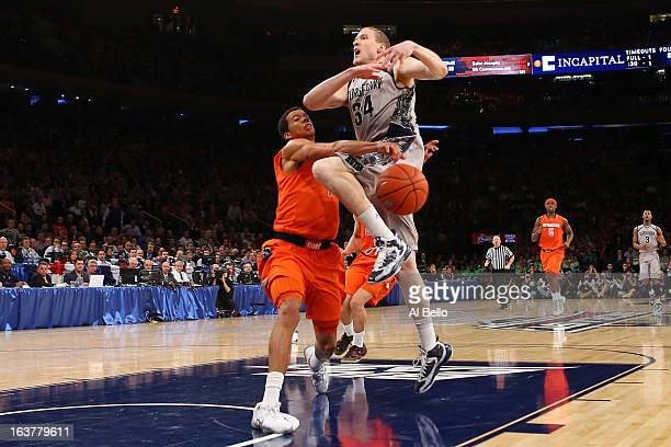 Nate Lubick of the Georgetown Hoyas has the ball knocked loses as he drove to the basket in the second half against Michael Carter-Williams of the...